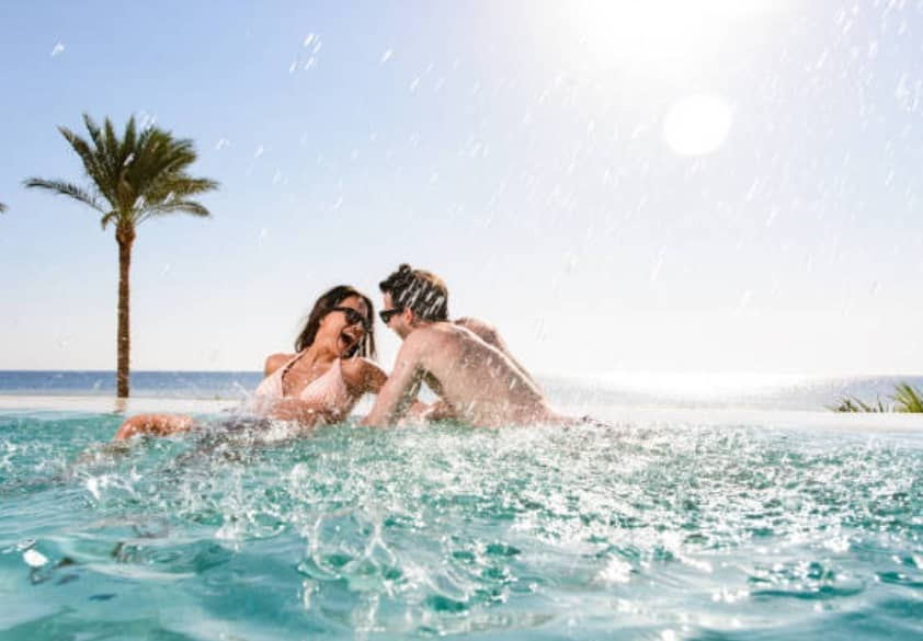 A happy young couple having fun in a swimming pool