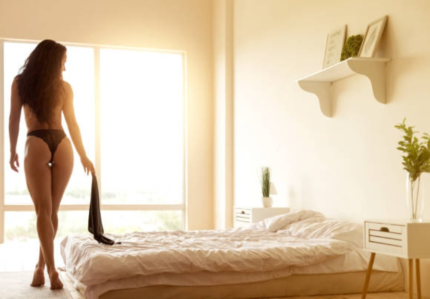 Sexy naked women flaunting her back while holding a soft fabric in the bedroom